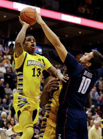 Marquette's Vander Blue (13) shoots against Connecticut's Tyler Olander (10) during the first half of an NCAA college basketball game, Tuesday, Jan. 1, 2013, in Milwaukee. (AP Photo/Jeffrey Phelps) Photo: JEFFREY PHELPS, Associated Press / FR59249 AP