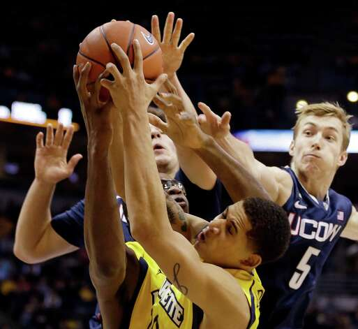 Marquette's Juan Anderson, bottom, reaches for a rebound with Connecticut's Niels Giffey (5) during the second half of an NCAA college basketball game, Tuesday, Jan. 1, 2013, in Milwaukee. (AP Photo/Jeffrey Phelps) Photo: JEFFREY PHELPS, Associated Press / FR59249 AP