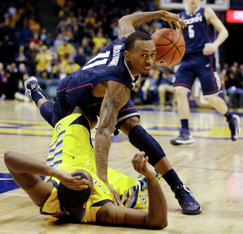 Connecticut's Ryan Boatright, top, tumbles over Marquette's Davante Gardner in overtime of an NCAA college basketball game, Tuesday, Jan. 1, 2013, in Milwaukee. Marquette won 82-76 in overtime. (AP Photo/Jeffrey Phelps) Photo: JEFFREY PHELPS, Associated Press / FR59249 AP