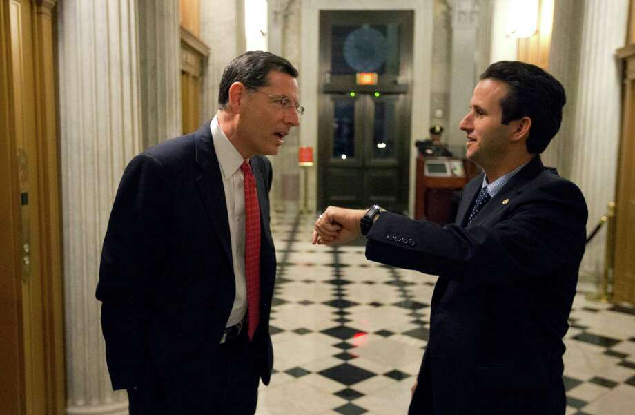 Sen. John Barrasso, left, R-Wyo., talks with Sen. Brian Schatz, D-Hawaii, who holds up his watch, near the Senate chambers after a vote on the fiscal cliff, on Capitol Hill Tuesday, Jan. 1, 2013 in Washington. The Senate passed legislation early New Year's Day to neutralize a fiscal cliff combination of across-the-board tax increases and spending cuts that kicked in at midnight. (AP Photo/Alex Brandon) Photo: Alex Brandon, STF / AP