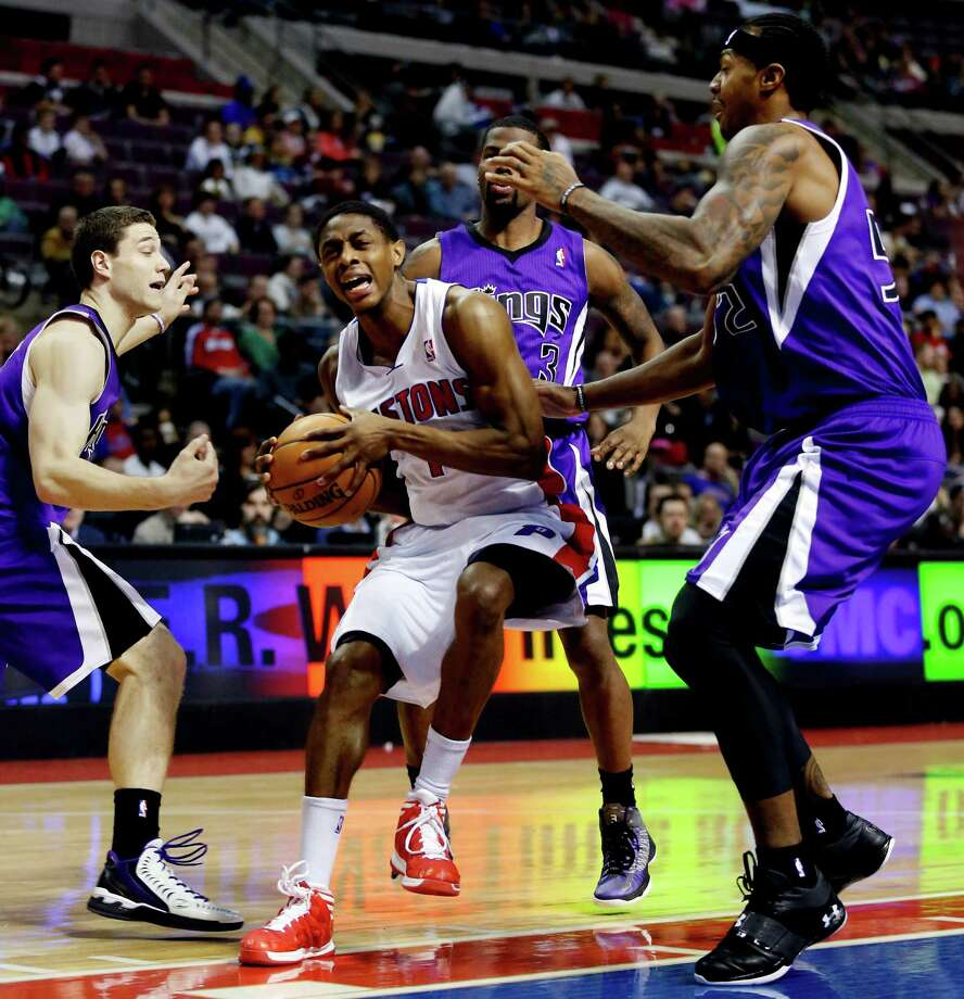 Detroit Pistons guard Brandon Knight, center, is surrounded by Sacramento Kings guard Jimmer Fredette, left, guard Aaron Brooks (3) and forward James Johnson, right, while going to the basket in the second half of an NBA basketball game, Tuesday, Jan. 1, 2013, in Auburn Hills, Mich. Knight scored 20 points in a 103-97 win. (AP Photo/Duane Burleson) Photo: Duane Burleson