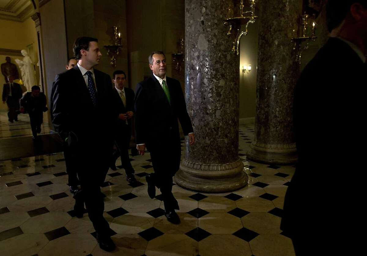 """Speaker of the House John Boehner, R-Ohio, center, returns to his office from the House chamber, as talks continue regarding the """"fiscal cliff"""" bill passed by the Senate Monday night, on Tuesday, Jan. 1, 2013 at the Capitol in Washington. (AP Photo/Jacquelyn Martin)"""