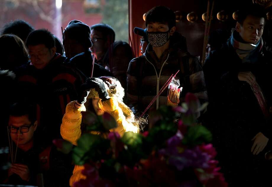 A Chinese woman holds incense in the air as she is struck by a beam of sunlight while offering prayers with others on the first day of the New Year at the Yonghegong Lama Temple in Beijing Tuesday, Jan. 1, 2013. (AP Photo/Andy Wong) Photo: Andy Wong, Associated Press