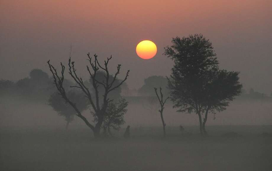 An Indian walks surrounded by fog as the sun rises in Ajmer, India, Tuesday, Jan. 1, 2013. North India continues to face extreme weather conditions with dense fog affecting flights and trains. (AP Photo/Deepak Sharma) Photo: Deepak Sharma, Associated Press