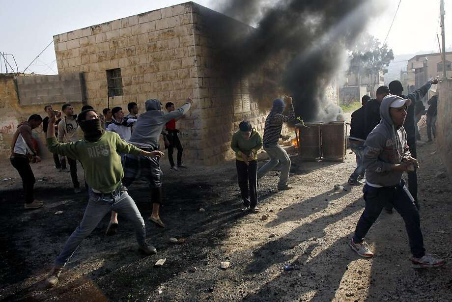 Palestinians hurl stones at Israeli soldiers, not seen, during clashes in the West Bank village of Tamoun, near Jenin, Tuesday, Jan. 1, 2013. Palestinians say a raid by Israeli soldiers disguised as vegetable vendors to seize members of a militant group has sparked clashes in the northern West Bank. (AP Photo/Mohammed Ballas) Photo: Mohammed Ballas, Associated Press