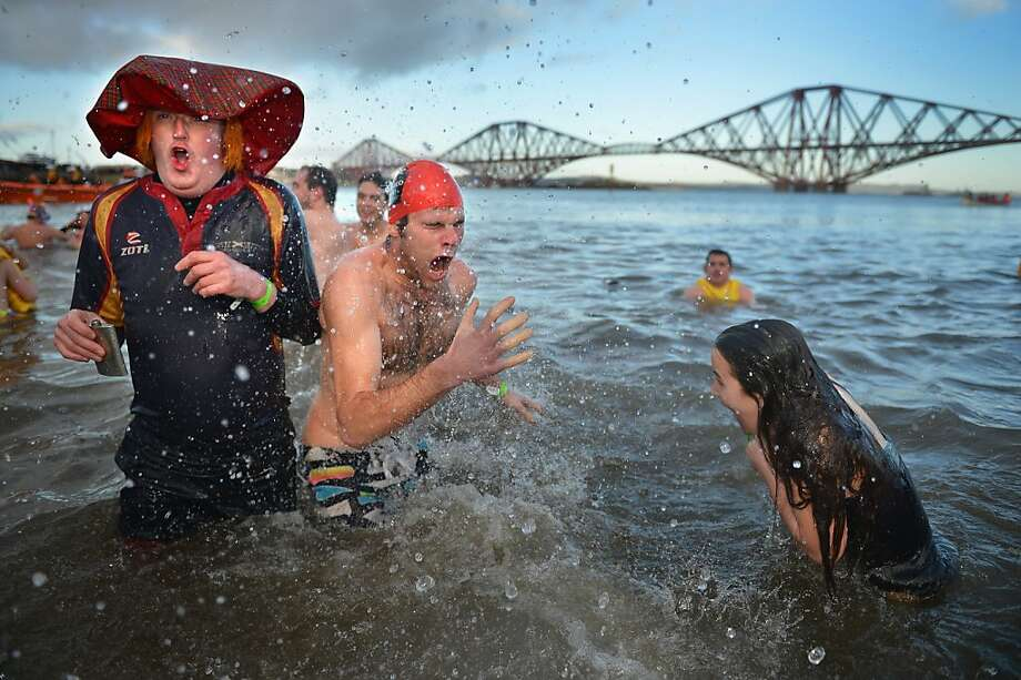 SOUTH QUEENSFERRY, SCOTLAND - JANUARY 01:  Over 1,000 New Year swimmers, many in costume, braved freezing conditions in the River Forth in front of the Forth Rail Bridge during the annual Loony Dook Swim on January 1, 2013 in South Queensferry, Scotland. Thousands of people gathered last night to see in the New Year at Hogmanay celebrations in towns and cities across Scotland.  (Photo by Jeff J Mitchell/Getty Images)  *** BESTPIX *** Photo: Jeff J Mitchell, Getty Images