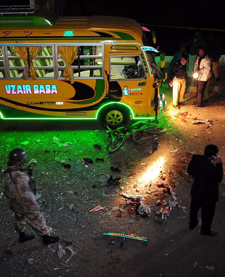 Pakistani security officials are pictured at the site of a bomb explosion in Karachi on January 1, 2013. A bomb planted on a motorbike wounded at least 21 people in Pakistan's largest city of Karachi, police said. The target of the attack appeared to be buses taking back activists after a joint rally organised by the city's dominant political party, the Muttahida Qaumi Movement (MQM), and Tehreek-e-Minhajul Quran -- the movement to follow the path of the Koran, led by Muslim scholar Tahir-ul Qadri. AFP PHOTO/RIZWAN TABASSUMRIZWAN TABASSUM/AFP/Getty Images Photo: Rizwan Tabassum, AFP/Getty Images