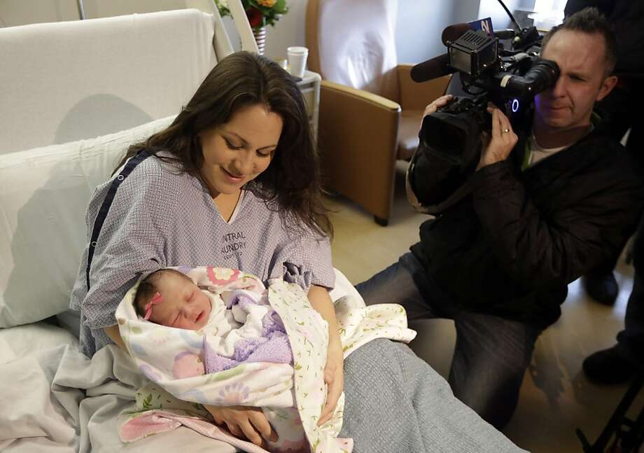 """Monica Rossano holds her daughter Anna-Sofia, who was born 12:01 a.m., during a news conference Tuesday, Jan. 1, 2013, at the Intermountain Medical Center, in Murray, Utah. """"It wasn't induced labor or anything. It was totally natural. We weren't trying to be the first,"""" Intermountain Medical Center spokesman Jason Carlton told The Associated Press. Photo: Rick Bowmer, Associated Press"""