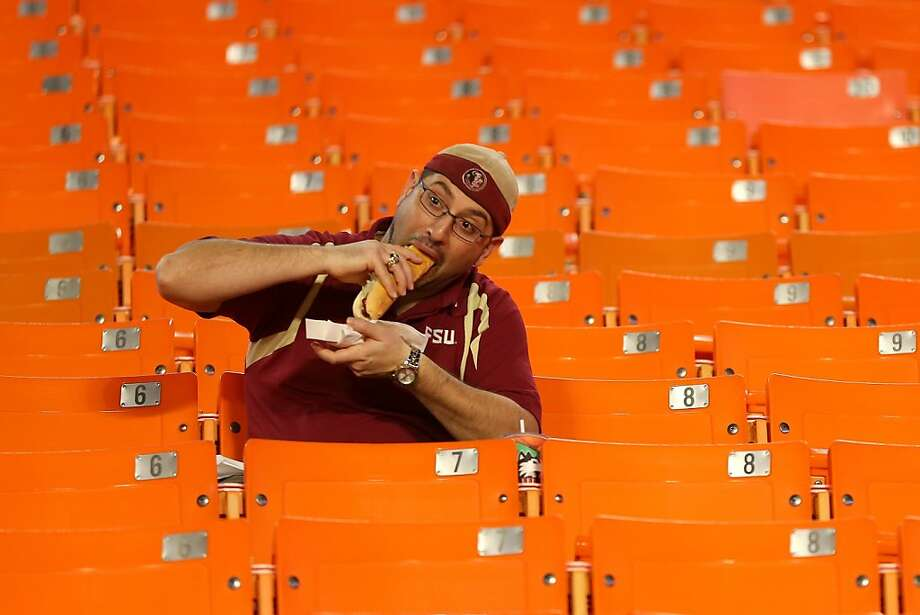 MIAMI GARDENS, FL - JANUARY 01:  A fan of the Florida State Seminoles eats a hotdog in the stands prior to Florida State plays Northern Illinois Huskies during the Discover Orange Bowl at Sun Life Stadium on January 1, 2013 in Miami Gardens, Florida. Photo: Mike Ehrmann, Getty Images