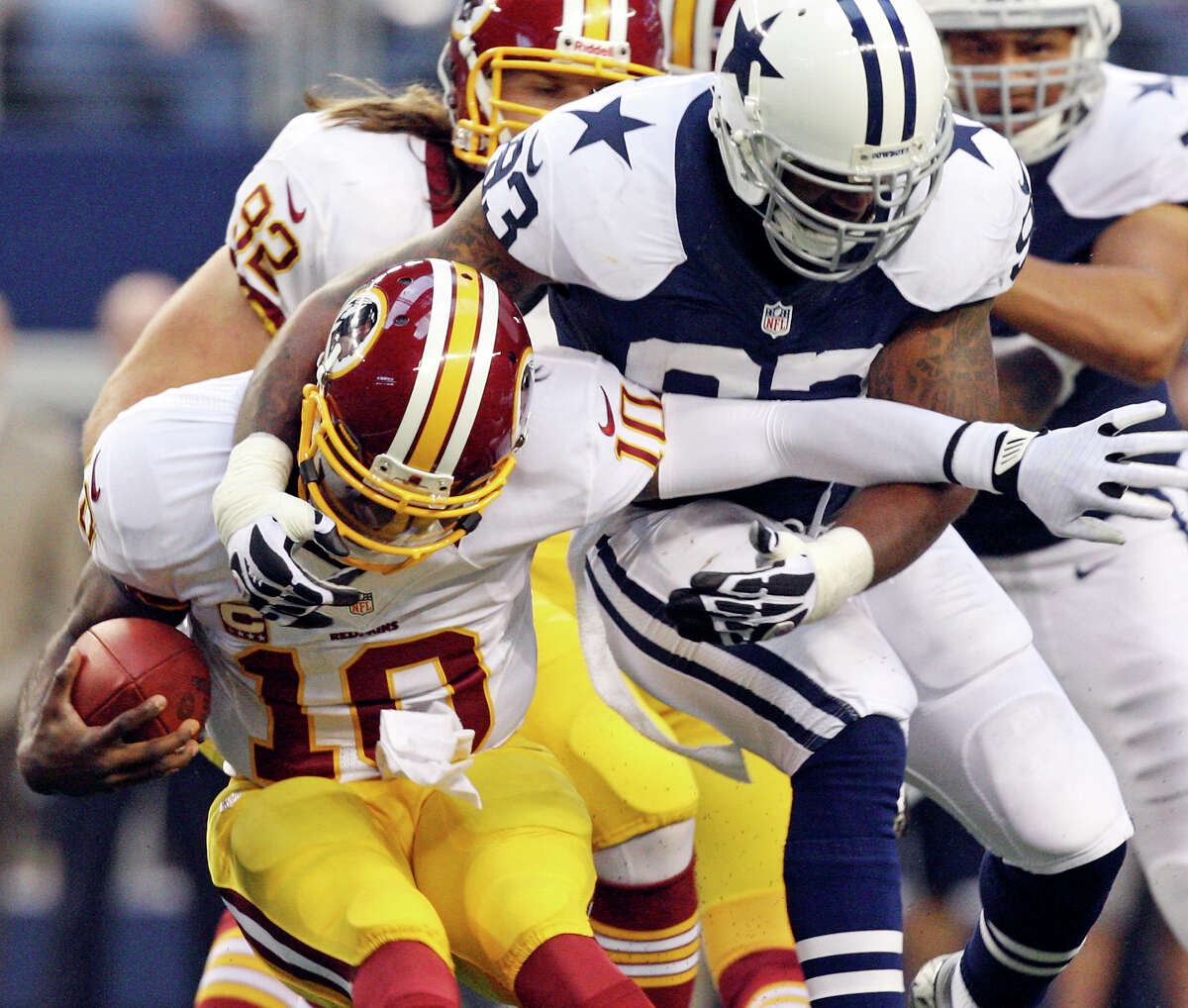 The Washington Redskins' Robert Griffin III is sacked by the Dallas Cowboys' Anthony Spencer during first half action Thursday, Nov. 22, 2012, at Cowboys Stadium in Arlington.