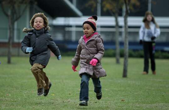 Jae Tolentino, 7, races his little sister Isale Tolentino, 5, down the hill at Discovery Green on Thursday, Dec. 27, 2012, in Houston. Dispite cold weather, the Tolentino children asked for a trip to the park and ice skating. Photo: Mayra Beltran, Houston Chronicle / © 2012 Houston Chronicle