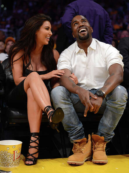 Kim Kardashian and Kanye West watch the video board from their courtside seats as the Los Angeles La