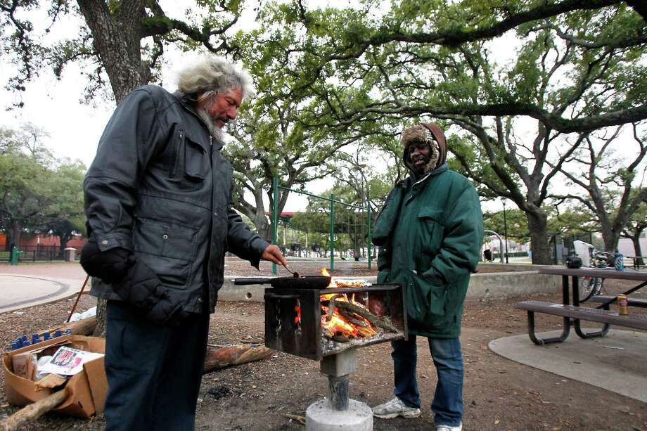 Flaco Ramirez, left, and James Adams, right, keep warm and cook breakfast at Peggy Park, Wednesday, Jan. 2, 2013, in Houston. The weather will be in the 40s throughout the day and will stay in the 50s until Sunday. Photo: Cody Duty, Houston Chronicle / © 2012 Houston Chronicle