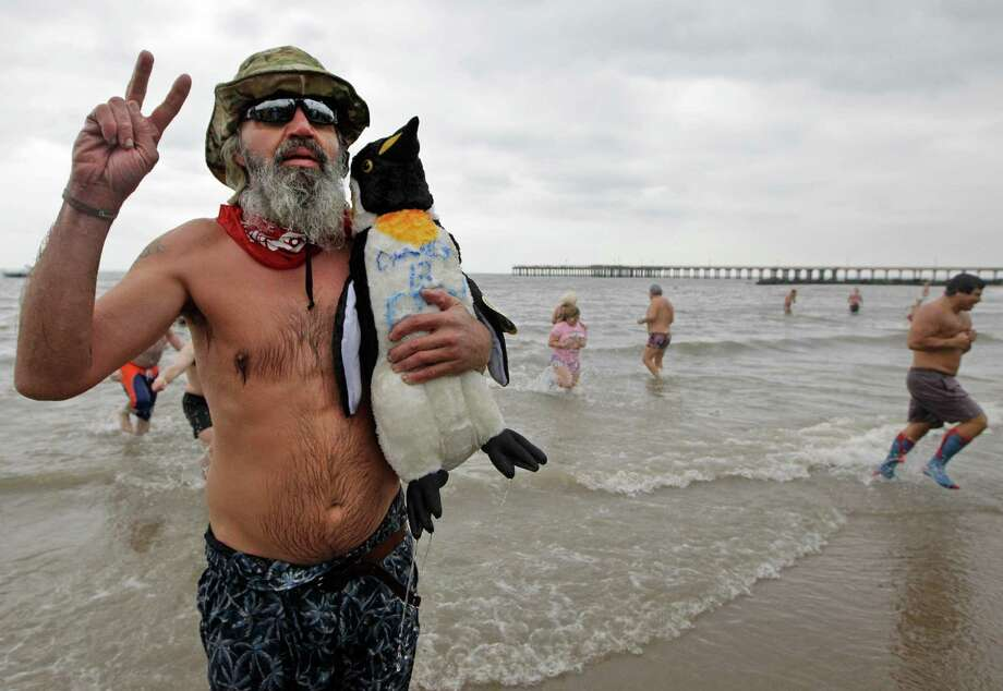 "Ed ""Road Dog"" Menley of Florida flashes a peace sign after emerging from the water carrying a wet stuffed penguin during the 110th annual Coney Island Polar Bear Club ocean swim at Coney Island in New York, Tuesday, Jan. 1, 2013. Menley said he is in New York volunteering with Superstorm Sandy cleanup efforts in Breezy Point. Photo: Kathy Willens, AP / AP"