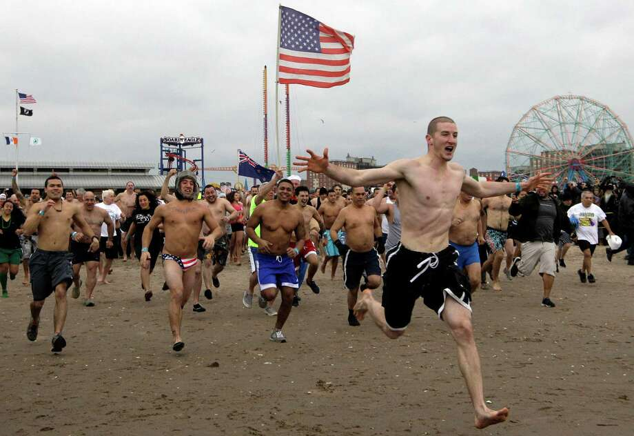 The first wave of several hundred swimmers rush to take a plunge in 30-degree temperatures during the 110th annual Coney Island Polar Bear Club ocean swim on New Year's Day at Coney Island in New York, Tuesday, Jan. 1, 2013. Photo: Kathy Willens, AP / AP