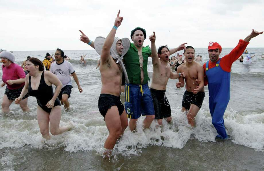 Swimmers celebrate after plunging in the water in 30-degree temperatures during the 110th annual Coney Island Polar Bear Club ocean swim at Coney Island in New York, Tuesday, Jan. 1, 2013. Photo: Kathy Willens, AP / AP