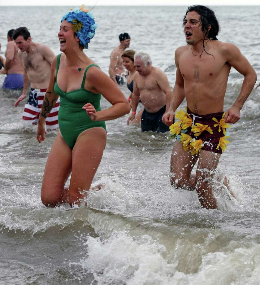 A couple takes the plunge on New Year's Day during the 110th annual Coney Island Polar Bear Club ocean swim at Coney Island in New York, Tuesday, Jan. 1, 2013. Photo: Kathy Willens, AP / AP