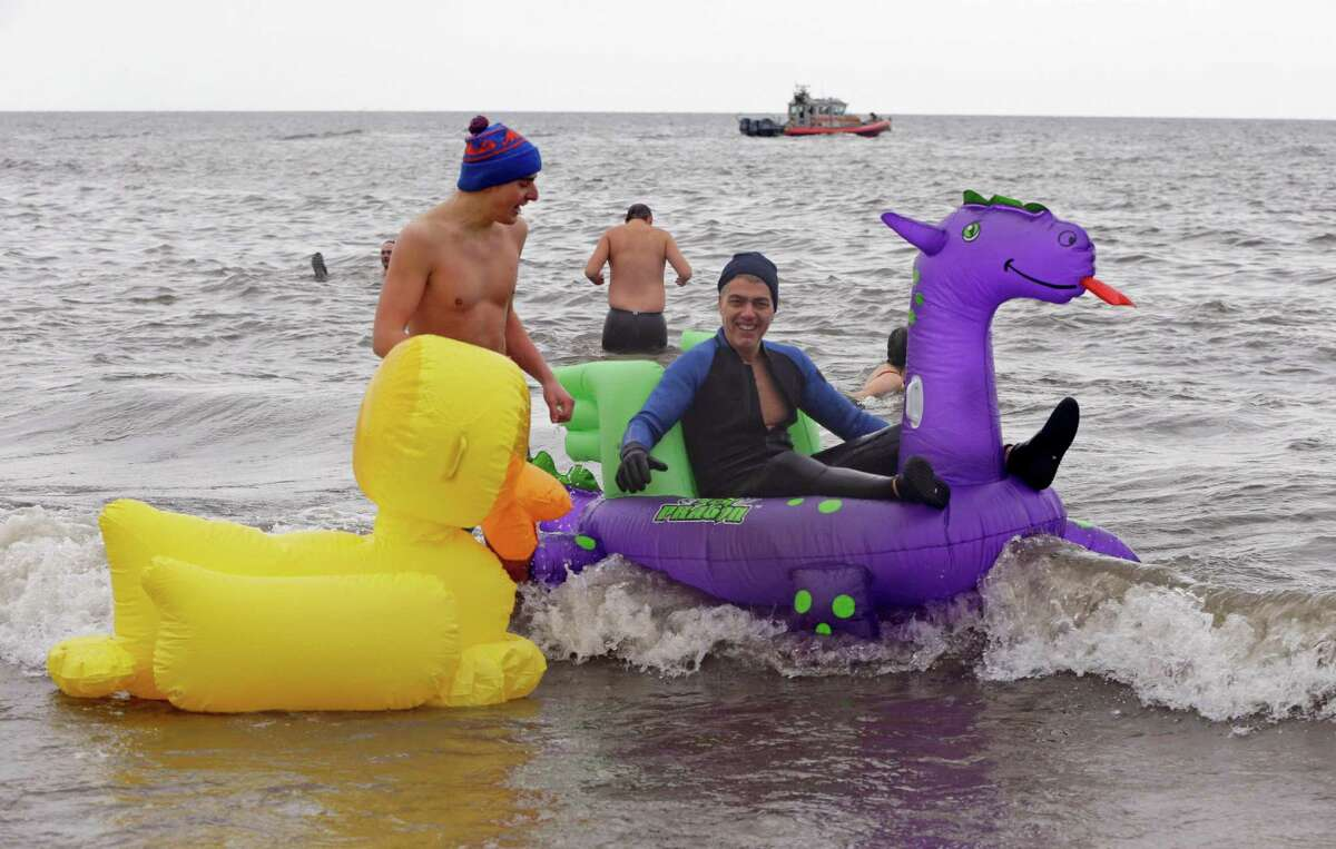 Two men use inflatable rafts at the water's edge in 30-degree temperatures during the 110th annual Coney Island Polar Bear Club ocean swim at Coney Island in New York, Tuesday, Jan. 1, 2013.