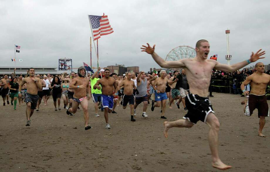 The first wave of swimmers willing to brave temperatures in the 30's head for the water during the 110th annual Coney Island Polar Bear Club ocean swim at Coney Island in New York, Tuesday, Jan. 1, 2013. Photo: Kathy Willens, AP / AP