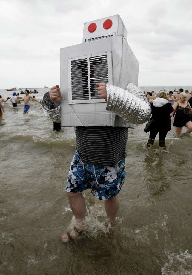 Picking up on a theme related to Superstorm Sandy, which hit Coney Island hard, a man dressed as a boiler tests the water during the 110th annual Coney Island Polar Bear Club ocean swim at Coney Island in New York, Tuesday, Jan. 1, 2013. Photo: Kathy Willens, AP / AP