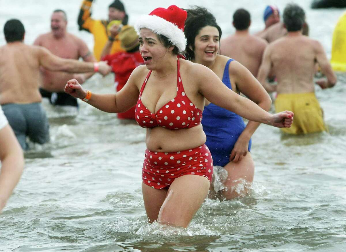 NEW YORK, NY - JANUARY 1: A woman reacts to the frigid water during the Coney Island Polar Bear Club's New Year's Day swim on January 1, 2013 in the Coney Island neighborhood of the Brooklyn borough of New York City. The annual event attracts hundreds who brave the icy Atlantic waters and temperatures in the upper 30's as a way to celebrate the first day of the new year.
