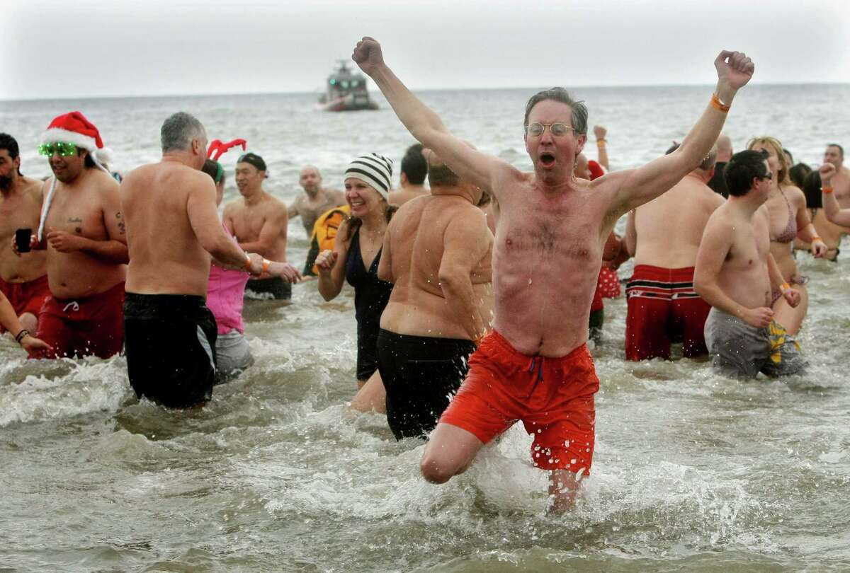 NEW YORK, NY - JANUARY 1: A man reacts after plunging into the frigid water during the Coney Island Polar Bear Club's New Year's Day swim on January 1, 2013 in the Coney Island neighborhood of the Brooklyn borough of New York City. The annual event attracts hundreds who brave the icy Atlantic waters and temperatures in the upper 30's as a way to celebrate the first day of the new year.
