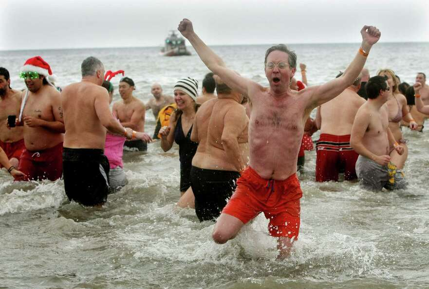 NEW YORK, NY - JANUARY 1: A man reacts after plunging into the frigid water during the Coney Island