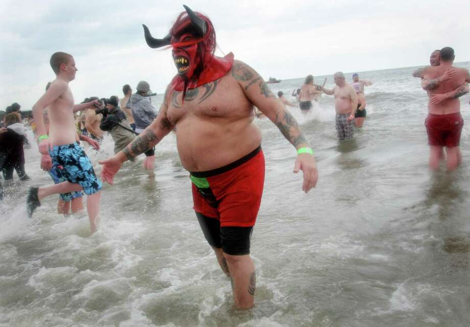 NEW YORK, NY - JANUARY 1:  A man wearing a monster mask takes part in the Coney Island Polar Bear Club's New Year's Day swim on January 1, 2013 in the Coney Island neighborhood of the Brooklyn borough of New York City. The annual event attracts hundreds who brave the icy Atlantic waters and temperatures in the upper 30's as a way to celebrate the first day of the new year. Photo: Monika Graff, Getty Images / 2013 Getty Images