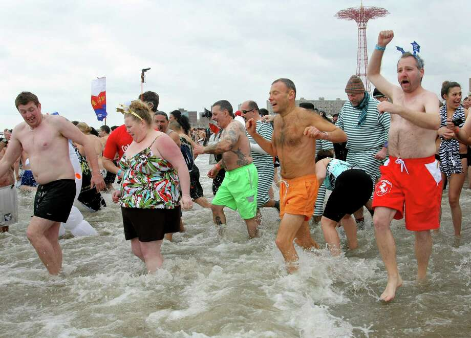 NEW YORK, NY - JANUARY 1:  People run into the chilly water as they take part in the Coney Island Polar Bear Club's New Year's Day swim on January 1, 2013 in the Coney Island neighborhood of the Brooklyn borough of New York City. The annual event attracts hundreds who brave the icy Atlantic waters and temperatures in the upper 30's as a way to celebrate the first day of the new year. Photo: Monika Graff, Getty Images / 2013 Getty Images