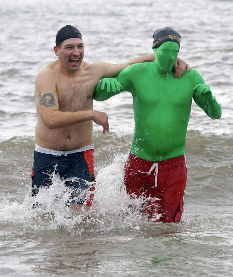 Two men react as they splash around at the water's edge after taking a dip during the 110th annual Coney Island Polar Bear Club ocean swim at Coney Island in New York, Tuesday, Jan. 1, 2013. Photo: Kathy Willens, AP / AP