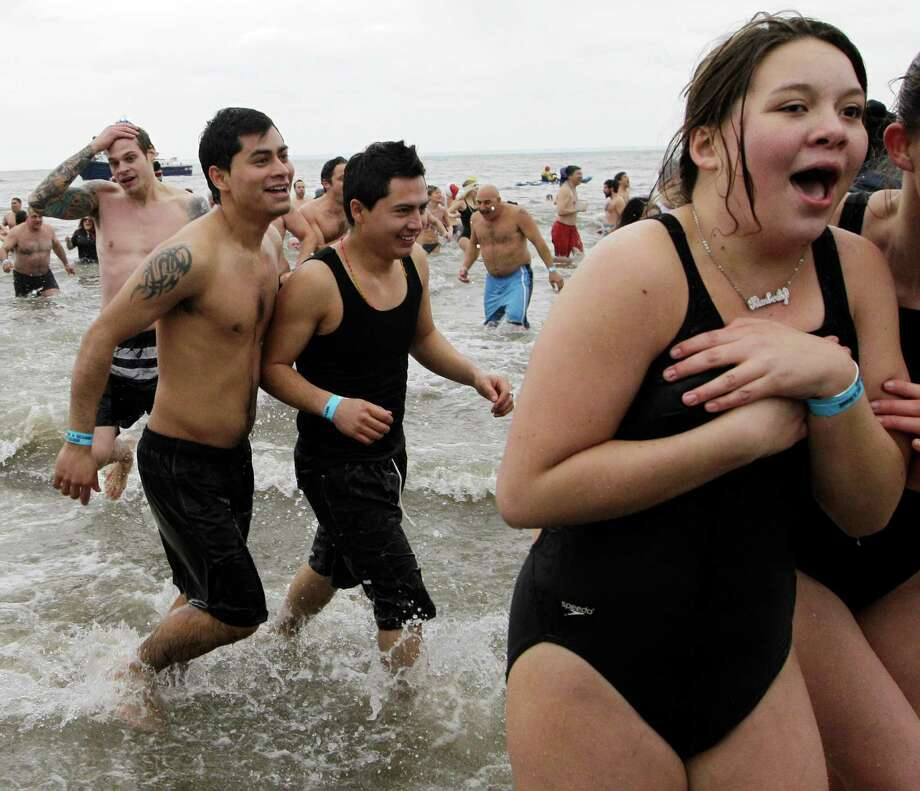 People react after taking the plunge in 30-degree temperatures during the 110th annual Coney Island Polar Bear Club ocean swim at Coney Island in New York, Tuesday, Jan. 1, 2013. Photo: Kathy Willens, AP / AP