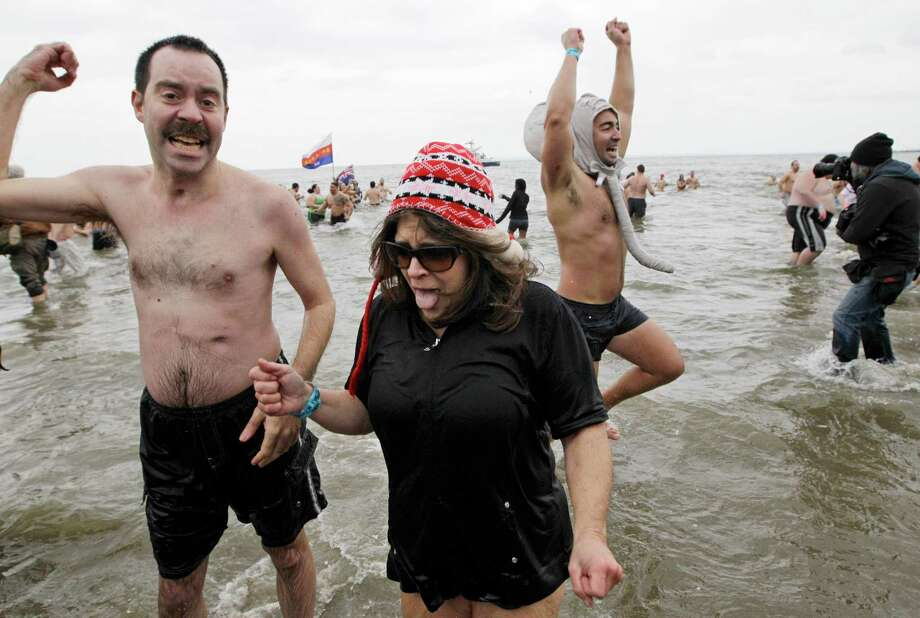 A man and a woman react after plunging into the ocean in 30-degree temperatures during the 110th annual Coney Island Polar Bear Club ocean swim at Coney Island in New York, Tuesday, Jan. 1, 2013. Photo: Kathy Willens, AP / AP