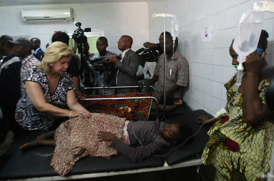 Dominique Ouattara (L), wife of President of The Ivory Coast Alassane Ouattara , stands next to a child, injured in a stampede, at the Cocody hospital in Abidjan, on January 1, 2013. At least 60 people died and at least dozens were injured as crowds stampeded overnight during celebratory New Year's fireworks, Ivory Coast rescue workers said on January 1, 2013. AFP PHOTO/HERVE SEVIHERVE SEVI/AFP/Getty Images Photo: HERVE SEVI, AFP/Getty Images / AFP