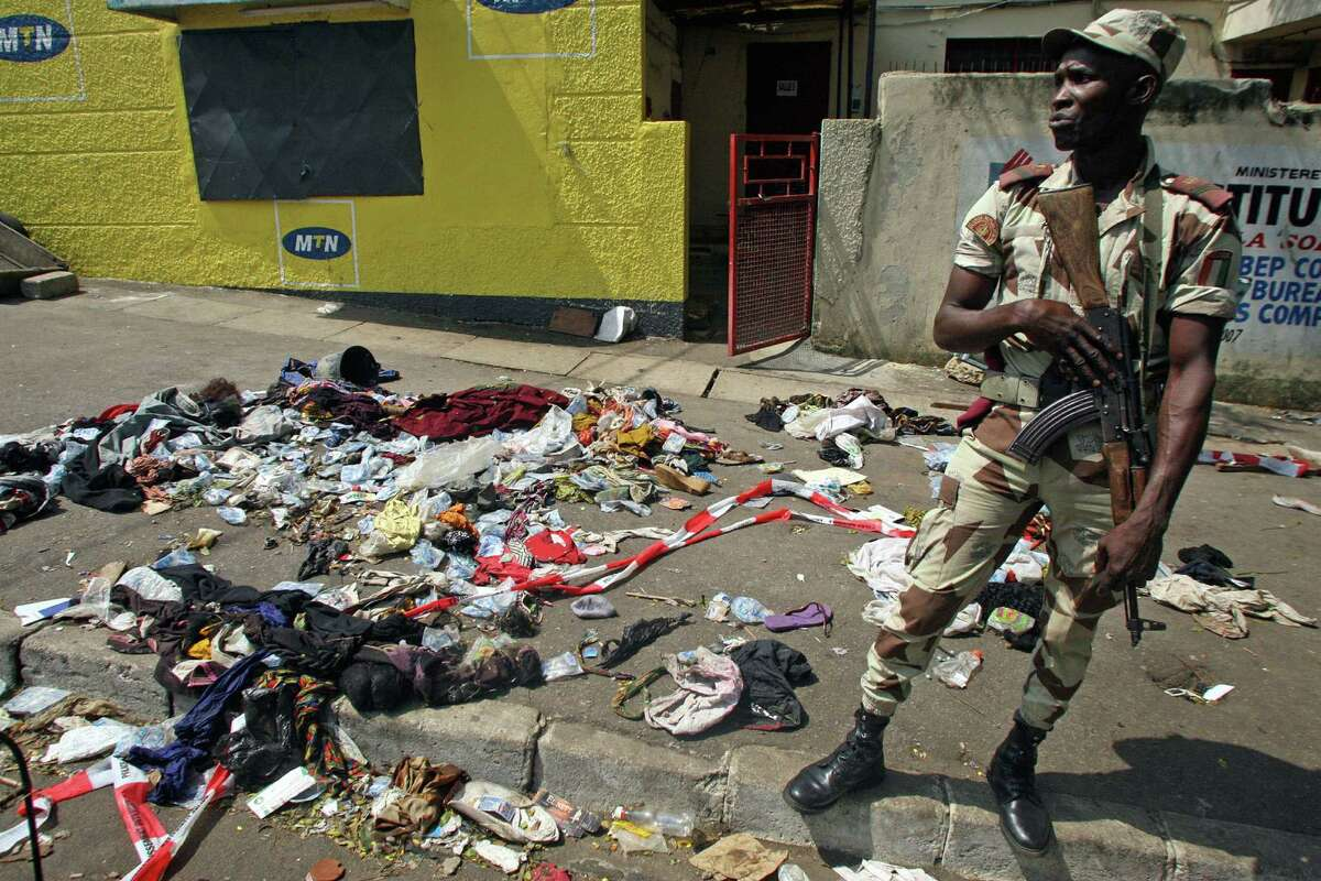An Ivory Coast troop stands next to the belongings of people involved in a deadly stampede in Abidjan, Ivory Coast, Tuesday, Jan. 1 2013. At least 61 people were killed early Tuesday in a stampede following a New Year's fireworks display in Abidjan, Ivory Coast's commercial center, said officials. The death toll is expected to rise, according to rescue workers.
