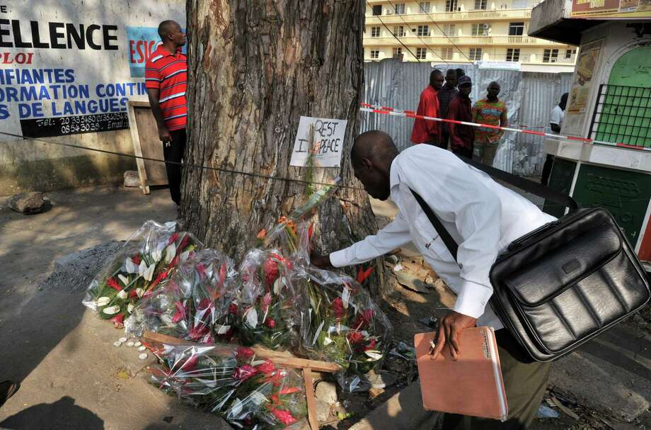 A man lays flowers on January 2, 2013 at a tree in the street of Abidjian where at least 60 persons died in a stampede among crowds gathered for celebratory New Year's Eve fireworks that also left dozens injured. Ivory Coast began today three days of national mourning.  AFP PHOTO / ISSOUF SANOGOISSOUF SANOGO/AFP/Getty Images Photo: ISSOUF SANOGO, AFP/Getty Images / AFP