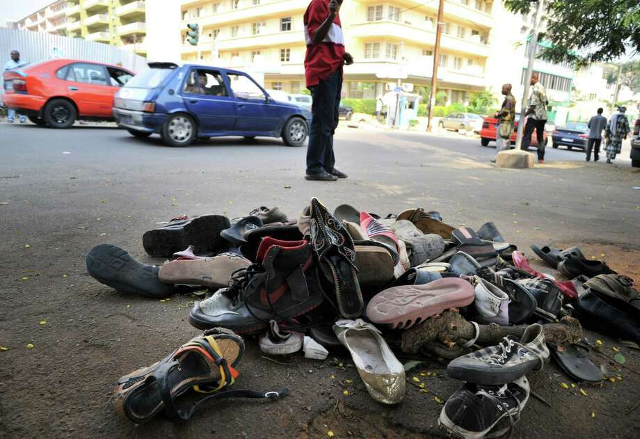 A pile of abandoned shoes is picutred on January 2, 2013 in the street of Abidjian where at least 60 persons died in a stampede among crowds gathered for celebratory New Year's Eve fireworks that also left dozens injured. Ivory Coast began today three days of national mourning.  AFP PHOTO / ISSOUF SANOGOISSOUF SANOGO/AFP/Getty Images Photo: ISSOUF SANOGO, AFP/Getty Images / AFP