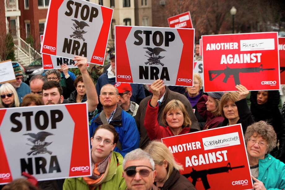 Protesters marching with the social activist group CREDO along with other concerned citizens descend on the offices of the NRA's (National Rifle Association)Capitol Hill lobbiest's office demanding the pro-gun lobby stand down in reaction to the shooting at Sandy Hook Elementary School December 17, 2012, in Washington, DC. Photo: PAUL J. RICHARDS, AFP/Getty Images / 2012 AFP
