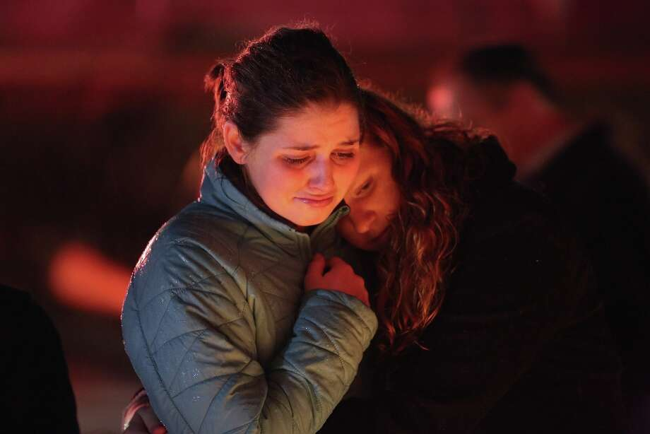 Rachel Berger, left, and Greta Waag embrace while visiting a makeshift memorial for shooting victims on December 18, 2012 in Newtown, Connecticut. Photo: John Moore, Getty Images / 2012 Getty Images