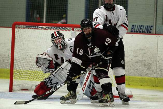 New Canaan Rams goalie Chrisopher Koennecke  fights his way off the screen of North Haven's Alec Rizzo during hockey aqction in Darien on Tuesday afternoon. The two squads battled to a 2-2 overtime tie. Photo: J. Gregory Raymond / Stamford Advocate Freelance;  © J. Gregory Raymond