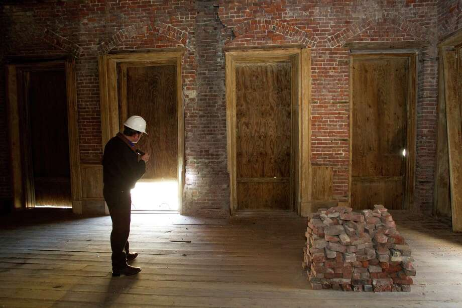 Rozier looks through the interior of the Hendley Building, being restored by Mitchell Historic Properties. Photo: Brett Coomer, Houston Chronicle / © 2012 Houston Chronicle