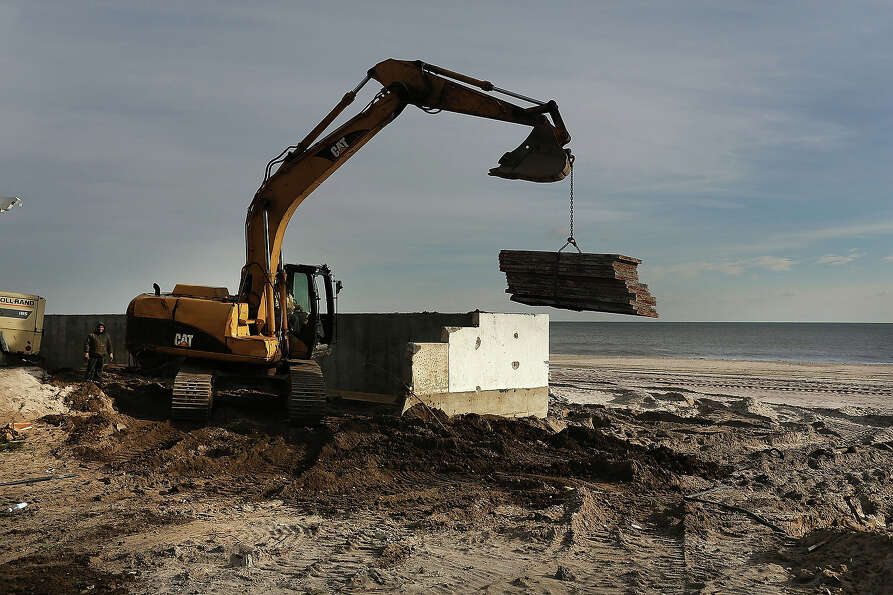 Construction workers build a new sea wall along the beach in the Belle Harbor neighborhood in the Ro