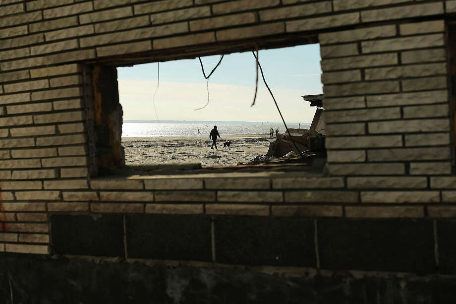 A man, seen through the window of a destroyed home, walks his dog along the beach in the Belle Harbor neighborhood in the Rockaways on January 2, 2013 in the Queens borough of New York City. Criticism, including by President Barack Obama, has been directed at the Republican House's decision to adjourn without passing a Hurricane Sandy aid bill. According to early estimates, Hurricane Sandy inflicted at least $50 to $60 billion in damage across the Northeast, making it one of the most destructive storms ever. Photo: Spencer Platt, Getty Images / 2013 Getty Images