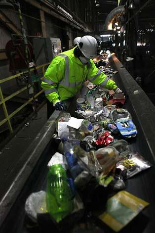 Workers at Recology in San Francisco sort recycled items as they move along on a conveyer belt. Many items are being stolen from residents' bins Photo: Liz Hafalia, The Chronicle