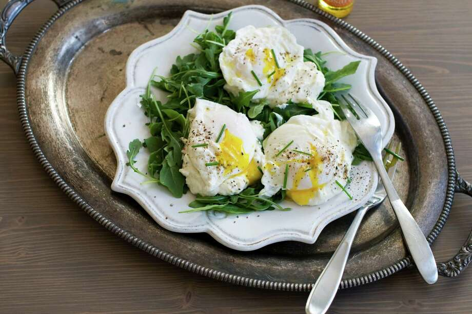 In this image taken Dec. 3, 2012, poached eggs over ricotta cheese on arugula are shown served on a plate in Concord, N.H. (AP Photo/Matthew Mead) Photo: MATTHEW MEAD