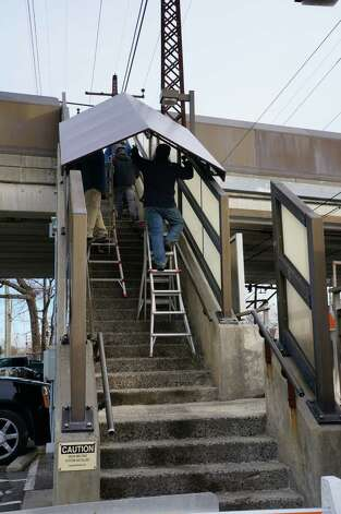 Canopies are being installed over the stairs at the downtown train station. Installation should take about a week to complete. Photo: Genevieve Reilly / Fairfield Citizen