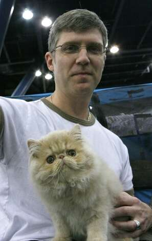 Jim Fleeker from Dallas holds his cat Chase, a cream Persian at the 2008 cat show. Photo: Steve Campbell, Houston Chronicle / Houston Chronicle