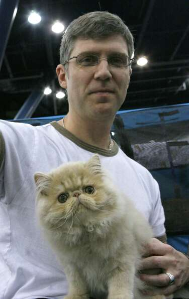 Jim Fleeker from Dallas holds his cat Chase, a cream Persian at the 2008 cat show.