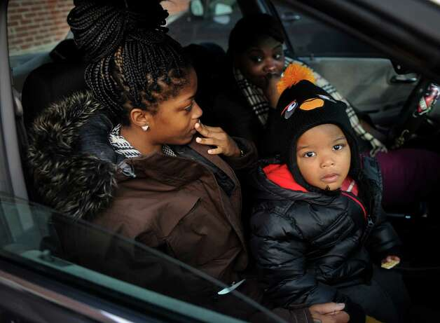Butler Business School students Shaniqua Vines, left, Latavia Warren, and Vines' son Zakhi Butler, 2, all of Stamford, react to hearing of the school's closing at 2710 North Avenue in Bridgeport on Wednesday, January 2, 2012. Photo: Brian A. Pounds