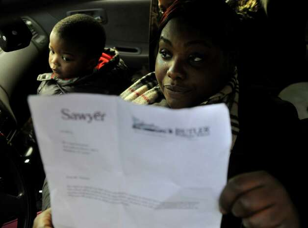 Butler Business School student Latavia Warren, of Stamford, shows the letter she received outside the closed school at 2710 North Avenue in Bridgeport on Wednesday, January 2, 2012. With Warren is fellow student Shaniqua Vines, also of Stamford, and Vines' son Zakhi Butler, 2. Photo: Brian A. Pounds