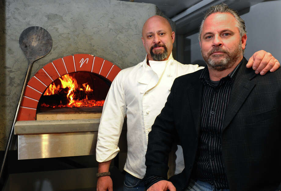 G-G's Wood Fired Pizza restaurant owners Gregory Pastorok and his brother George, right, pose with their Italian brick oven at the eatery in Milford, Conn. on Wednesday January 2, 2012. Photo: Christian Abraham / Connecticut Post
